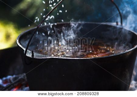 Preparation of pilaf on fire. Tourist bowler with food on bonfire cooking in the hike outdoor activities.