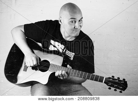 Music - Bald man play a black acoustic guitar on a white background. Monochrome. Vintage toning.