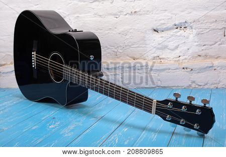 Musical instrument - Black cutaway acoustic guitar on a brick background and blue wooden floor.