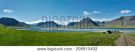 Travel to Iceland. beautiful sunrise over the ocean and fjord in Iceland. Icelandic landscape with mountains, blue sky and green grass on the foreground. View of the road to houses in the north-west of Iceland, on the Westfirdir peninsula