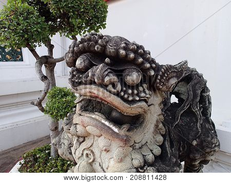 Stone figure of a Thai monster and a tree-bonsai