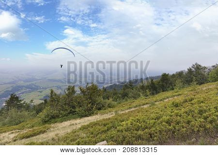 A flying paraglider against the blue sky in the morning fog of the Carpathian Mountains