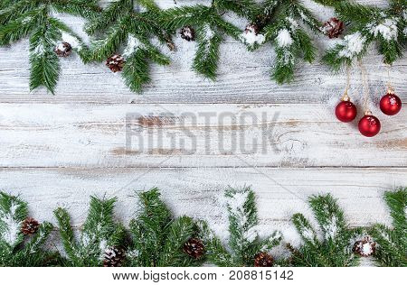 Snowy Christmas evergreen branches with handing red ornaments on rustic white wood background