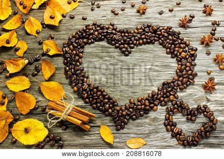 a heart of coffee beans strewn with autumn yellow leaves anise and cinnamon on a wooden surface. View from above