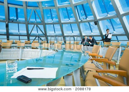 Customary conference room: glassy table chair large window poster