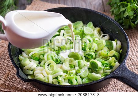 Stewing leek slices in a frying pan with cream
