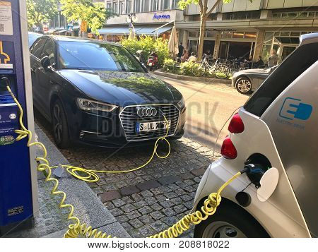 Stuttgart, Germany - October 14, 2017: Two electric cars are being charged by a power outlet in Stuttgart, one being an electro Smart, the other being an electro Audi.