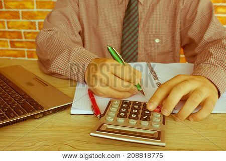 businessman and secretary making report calculating or checking balance. Internal Revenue Service inspects checks document with a laptop computer and calculator. Audit concept - Retro color