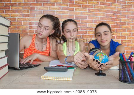 Three teenager girl doing homework at the table at home. Education and school concept. Young Girl student with pile of books and notes studying indoors