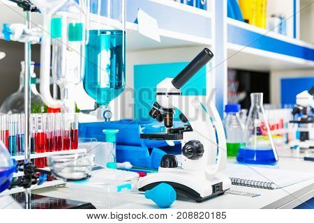 Table with scientific chemical laboratory equipment - microscope, test tubes with color liquid substance samples, vials, flasks, report documents etc. with selective focus effect