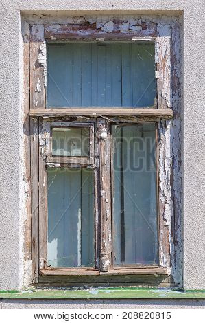 Old wooden window with a vent pane and the remains of white paint on the wall