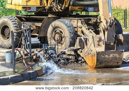 Excavator helps to eliminate the problem of breaking a pipe in the street on a hot summer day