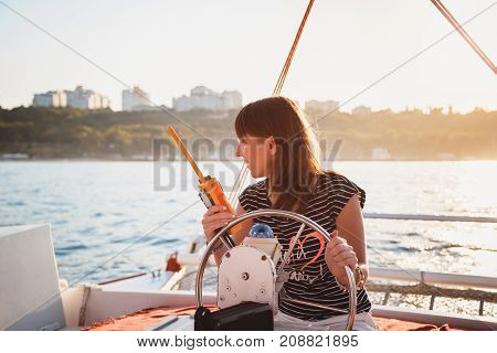Young pretty smiling girl in striped shirt and white shorts driving luxury yacht with walkie-talkie in hands, hot summer day, sunset.