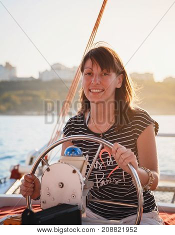 Young pretty smiling woman in striped shirt driving luxury yacht in sea, sunset.
