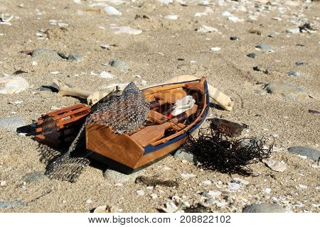 Toy wooden fishing boat sitting on the sea shore on a sunny day.
