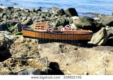 Miniature toy fishing boat sitting on large rock at the shore.