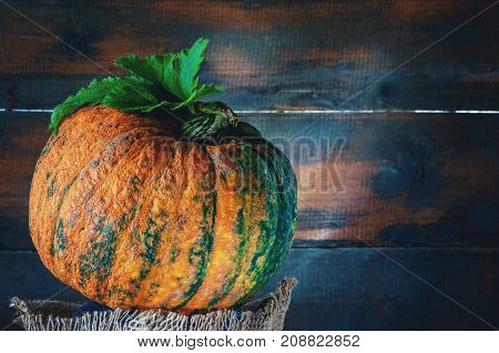 Ripe orange pumpkin rests on a wooden background in rustic style on wooden background. The horizontal frame.