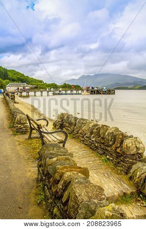 Bench and rock wall on the shore of Loch Lomond in Luss, Scotland