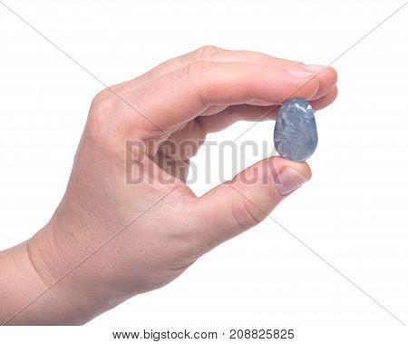 Woman's hand holding blue celestite polished palm stone isolated on white background