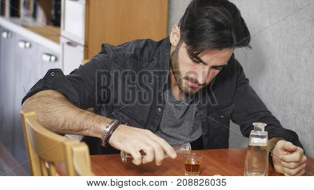 Young man sitting drinking alone at a table with two bottles of liquor alongside him sipping from shot glass to drown his sorrows