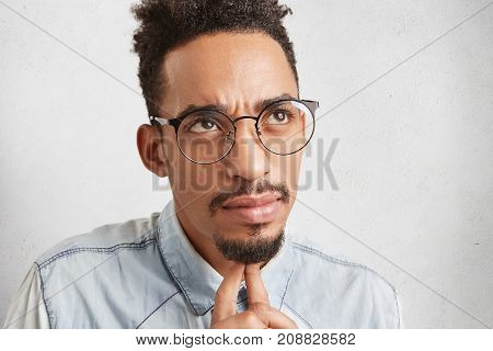 Candid Shot Of Pensive Man With Oval Face, Has Serious Facial Expression, Looks Up, Keeps Fingers Un