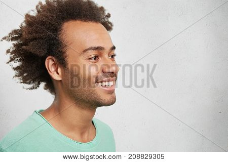 Sideways Portrait Of Afro American Cheerful Male With Crisp Hair, Smiles Gently, Wears Green Sweater