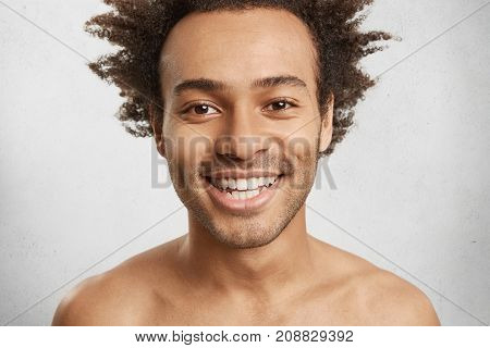 Headshot Of Naked Male With Appealing Appearance, Smiles Gladfully, Shows White Even Teeth, Has Good