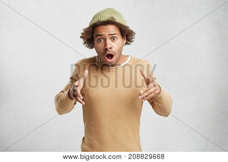 Fashionable Mixed Race Teenager In Trendy Hat And Sweater, Gestures In Bewilderment, Has Surprsied E
