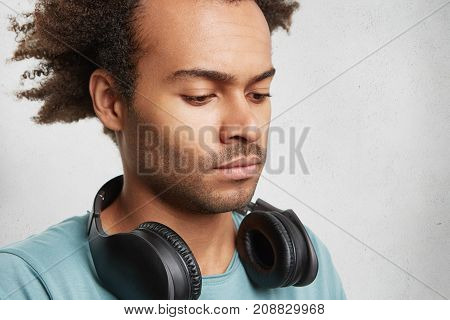 Serious Dark Skinned Teenager With Bushy Hairdo, Listens To Music With Headphones, Looks Seriously D