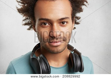 Close Up Portrait Of Mixed Race Dark Skinned Man With Bristle And Dark Eyes, Has Headphones, Listens