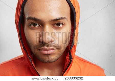 Close Up Portrait Of Attractive Young Man Wears Hood, Being Wet To Skin After Running At Rainy Weath