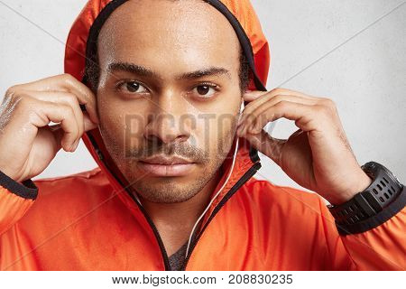 Close Up Portrait Of Wet Handsome Guy Holds Hand On Earphones, Listens Loud Audio, Wears Watch And O