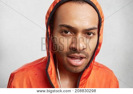 Portrait Of Wet Dark Skinned Male Listens To Music, Wears Hoody, Has Walk On Rainy Day, Looks Confid