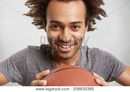 People, Active Lifestyle And Sport Concept. Cheerful Male Teenager With Afro Hairstyle, Keeps Basket