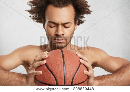 Serious Man With Bristle, Dark Skin And Curly Hairstyle Holds Basket Ball, Closes Eyes, Prays For Go