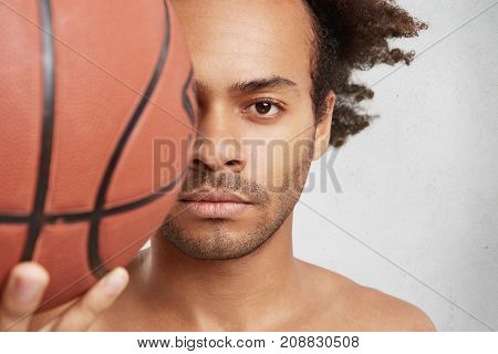 Close Up Portrait Of Successful Basketball Player Holds Ball In Foreground, Has Rest After Long Exha