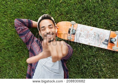 Horizontal Portrait Of Joyful Bearded Male Skateboarder Lies On Green Grass Near Skateboard, Listens