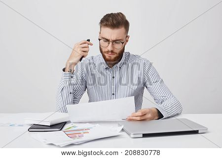 Horizontal Portrait Of Attractive Beatded Male Manager, Sits At Office, Surrounded With Laptop, Docu