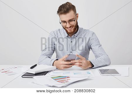 Stylish Man Has Trendy Hairdo Types Messages On Smart Phone, Sits On Work Place Surrounded With Pape