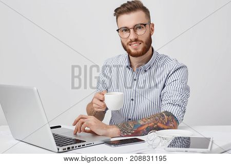 Delightful Male Freelancer With Thick Beard, Wears Spectacles, Has Tattooes, Works Remotely, Keyboar