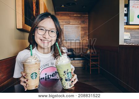 CHIANG RAI, THAILAND- July-02-2017 : Asian girl holding a Venti Starbucks frappuccino Irish coffee and Green tea latte frappuccino in Starbucks coffee shop.