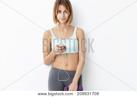 Portrait Of Beautiful Fit Female With Short Hairstyle, Wears Top And Leggins, Listens To Audio Track