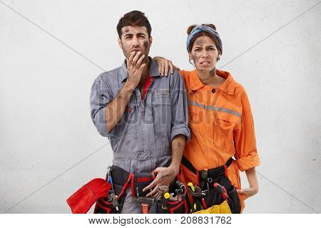 Upset Stressful Female And Male Technicians, Have Exhausted And Tired Expressions, Wears Uniform And