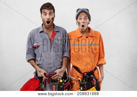 Isolated Studio Shot Of Untidy Female And Male Carpenters Look With Bugged Eyes And Jaw Dropped Out,