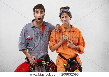 Astonished And Displeased Female And Male Technicians See That Water Leaks In Kitchen, Much Water On