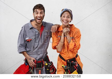 Horizontal Portrait Of Happy Talented Professional Construction Workers Work Together As Team, Smile