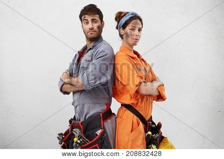 Portrait Of Confident Handyman And His Female Colleague Stand Back To Each Other, Keep Hands Folded,