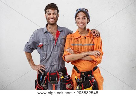 Glad Positive Maintenance Workers Stand Close To Each Other, Have Tired But Delightful Expressions,