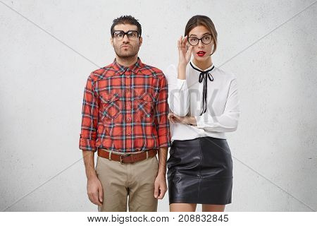 Serious Female And Male Wonks In Spectacles And Formal Clothes, Have Puzzled And Strict Expressions,