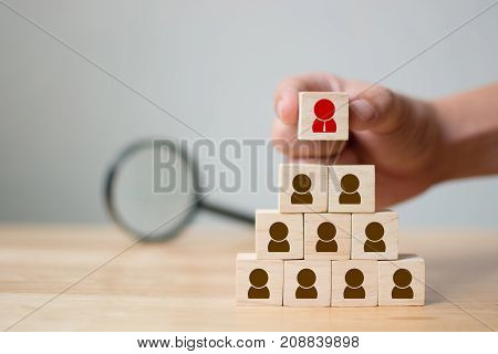 Human resource management and recruitment business concept Hand putting wood cube block on top pyramid and magnifying glass Copy space
